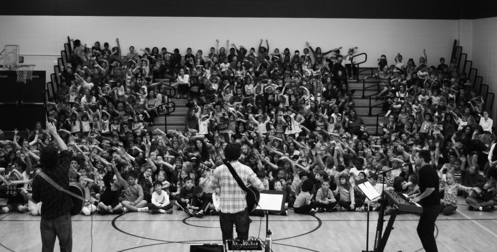 Jay (left), Barefoot Truth Lead singer Will Evans and Wayno (right) perform and talk to an elementary school in Indiana about music, business, and healthy living